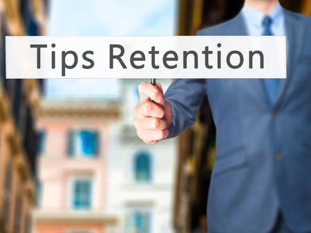 retention: Tips Retention - Businessman hand holding sign. Business, technology, internet concept. Stock Photo