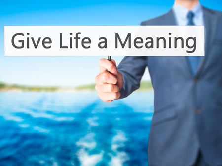 subsistence: Give Life a Meaning - Businessman hand holding sign. Business, technology, internet concept. Stock Photo Stock Photo