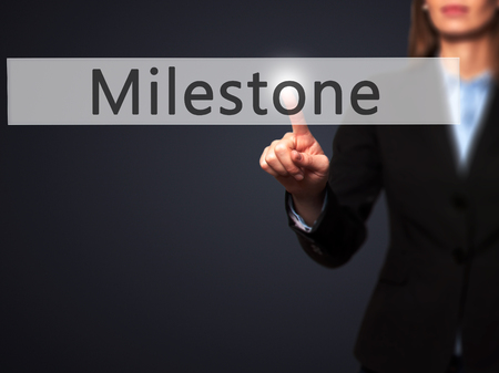 milestone: Milestone - Businesswoman hand pressing button on touch screen interface. Business, technology, internet concept. Stock Photo