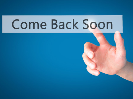 will return: Come Back Soon - Hand pressing a button on blurred background concept . Business, technology, internet concept. Stock Photo Stock Photo