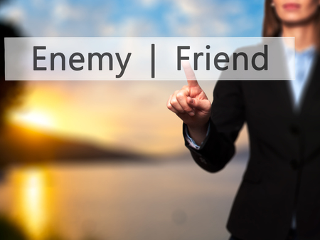 enemy: Enemy  Friend - Businesswoman hand pressing button on touch screen interface. Business, technology, internet concept. Stock Photo
