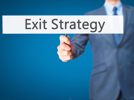 downsize: Exit Strategy - Businessman hand holding sign. Business, technology, internet concept. Stock Photo Stock Photo