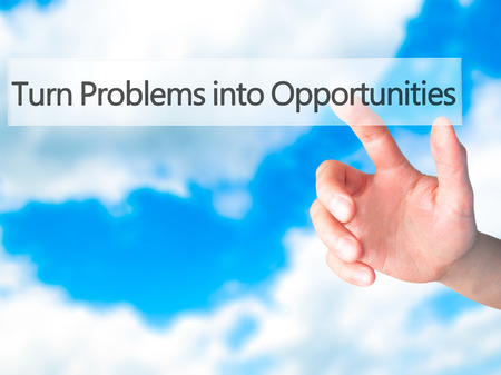 Turn Problems into Opportunities - Hand pressing a button on blurred background concept . Business, technology, internet concept. Stock Photo