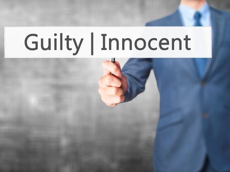 innocent: Guilty Innocent - Businessman hand holding sign. Business, technology, internet concept. Stock Photo Stock Photo