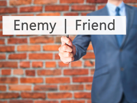 enemy: Enemy  Friend - Businessman hand holding sign. Business, technology, internet concept. Stock Photo