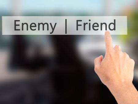 duplicitous: Enemy  Friend - Hand pressing a button on blurred background concept . Business, technology, internet concept. Stock Photo