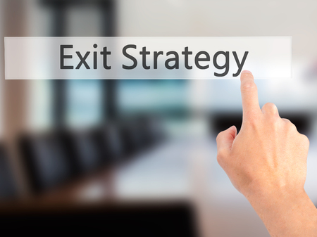 terminating: Exit Strategy - Hand pressing a button on blurred background concept . Business, technology, internet concept. Stock Photo Stock Photo