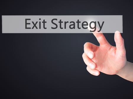 exiting: Exit Strategy - Hand pressing a button on blurred background concept . Business, technology, internet concept. Stock Photo Stock Photo