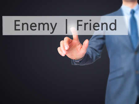 enemy: Enemy  Friend - Businessman hand pressing button on touch screen interface. Business, technology, internet concept. Stock Photo Stock Photo