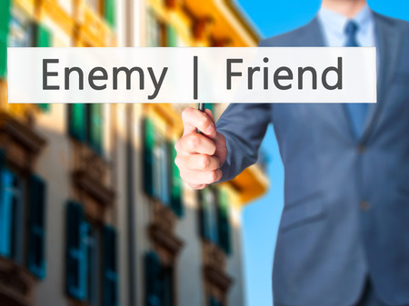 untrue: Enemy  Friend - Businessman hand holding sign. Business, technology, internet concept. Stock Photo