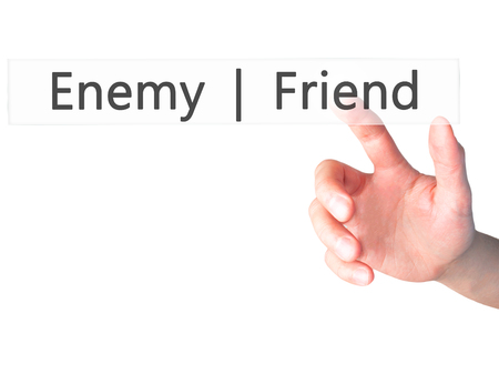 untrustworthy: Enemy  Friend - Hand pressing a button on blurred background concept . Business, technology, internet concept. Stock Photo
