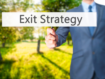 exiting: Exit Strategy - Businessman hand holding sign. Business, technology, internet concept. Stock Photo Stock Photo