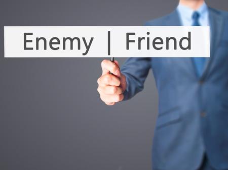 duplicitous: Enemy  Friend - Businessman hand holding sign. Business, technology, internet concept. Stock Photo