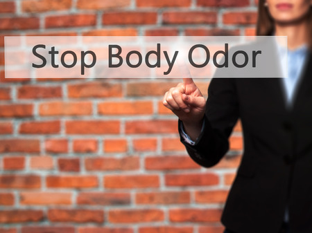 odor: Stop Body Odor - Businesswoman hand pressing button on touch screen interface. Business, technology, internet concept. Stock Photo