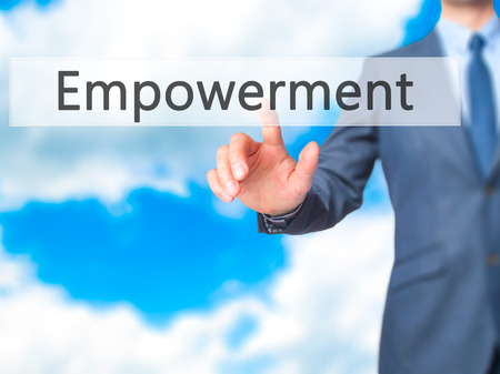 empowerment: Empowerment - Businessman hand pressing button on touch screen interface. Business, technology, internet concept. Stock Photo Stock Photo