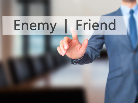 untrustworthy: Enemy  Friend - Businessman hand pressing button on touch screen interface. Business, technology, internet concept. Stock Photo Stock Photo