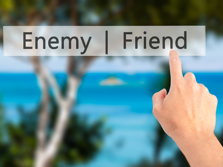 pretender: Enemy  Friend - Hand pressing a button on blurred background concept . Business, technology, internet concept. Stock Photo