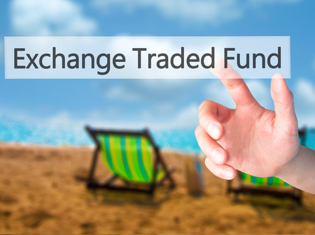 traded: Exchange Traded Fund - Hand pressing a button on blurred background concept . Business, technology, internet concept. Stock Photo
