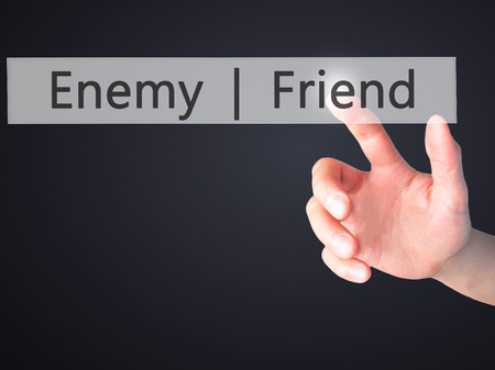 Enemy  Friend - Hand pressing a button on blurred background concept . Business, technology, internet concept. Stock Photo