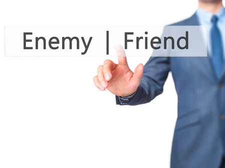 pretender: Enemy  Friend - Businessman hand pressing button on touch screen interface. Business, technology, internet concept. Stock Photo Stock Photo