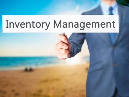 stockroom: Inventory Management - Businessman hand holding sign. Business, technology, internet concept. Stock Photo