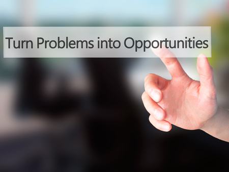 feasible: Turn Problems into Opportunities - Hand pressing a button on blurred background concept . Business, technology, internet concept. Stock Photo