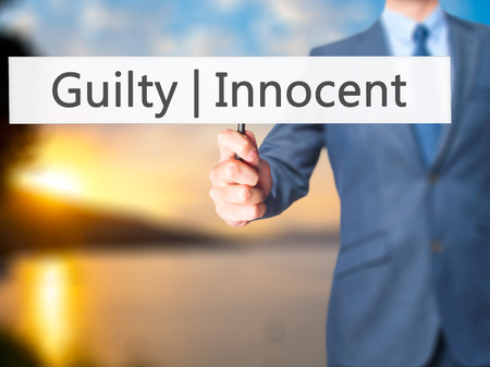 presumption: Guilty Innocent - Businessman hand holding sign. Business, technology, internet concept. Stock Photo Stock Photo