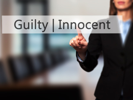 innocent: Guilty Innocent - Businesswoman hand pressing button on touch screen interface. Business, technology, internet concept. Stock Photo Stock Photo