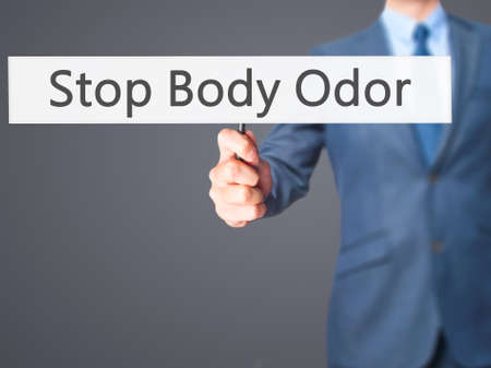 halitosis: Stop Body Odor - Businessman hand holding sign. Business, technology, internet concept. Stock Photo
