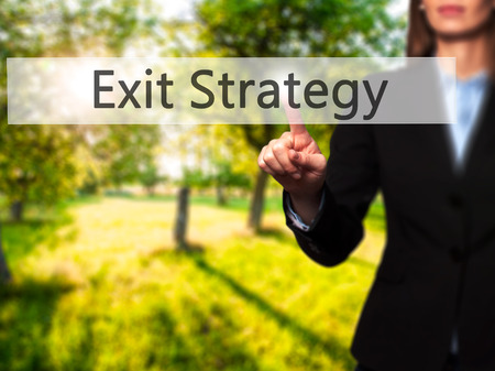 downsize: Exit Strategy - Businesswoman hand pressing button on touch screen interface. Business, technology, internet concept. Stock Photo