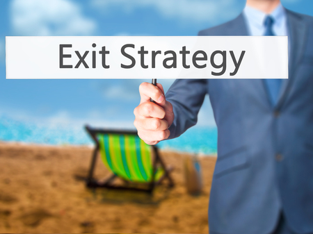 terminating: Exit Strategy - Businessman hand holding sign. Business, technology, internet concept. Stock Photo Stock Photo