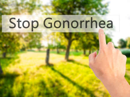 red condom: Stop Gonorrhea - Hand pressing a button on blurred background concept . Business, technology, internet concept. Stock Photo