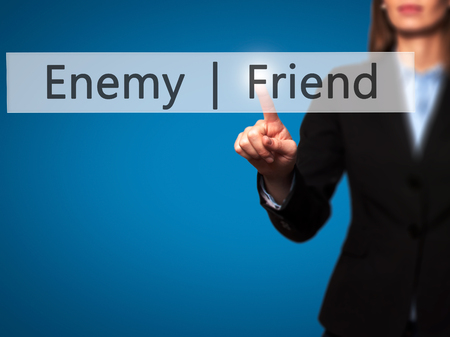 Enemy  Friend - Businesswoman hand pressing button on touch screen interface. Business, technology, internet concept. Stock Photo
