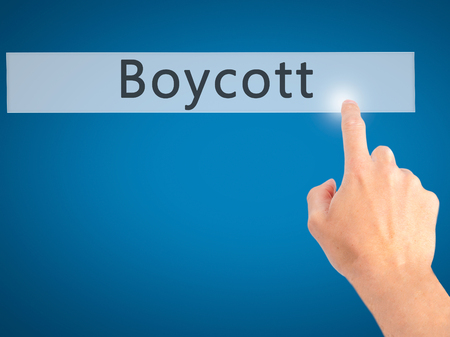 boycott: Boycott - Hand pressing a button on blurred background concept . Business, technology, internet concept. Stock Photo Stock Photo