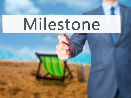 milestone: Milestone - Businessman hand holding sign. Business, technology, internet concept. Stock Photo