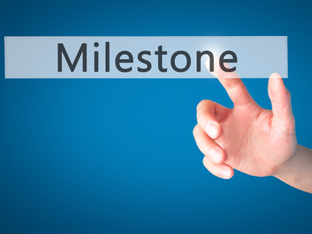 milestone: Milestone - Hand pressing a button on blurred background concept . Business, technology, internet concept. Stock Photo