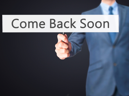 will return: Come Back Soon - Businessman hand holding sign. Business, technology, internet concept. Stock Photo