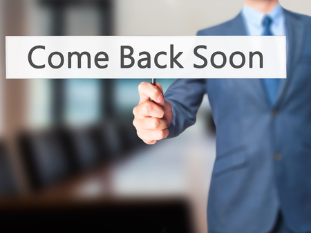 come on: Come Back Soon - Businessman hand holding sign. Business, technology, internet concept. Stock Photo