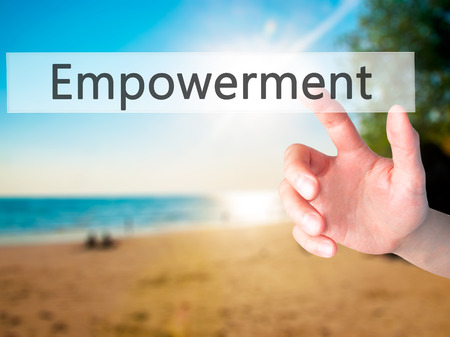 enable: Empowerment - Hand pressing a button on blurred background concept . Business, technology, internet concept. Stock Photo Stock Photo