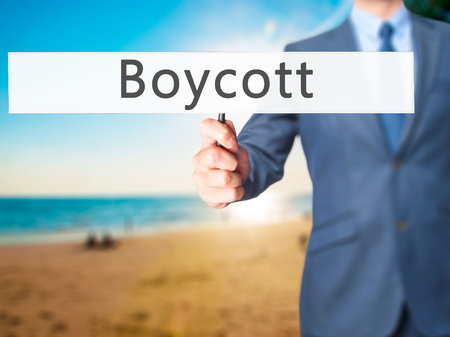 consumer rights: Boycott - Businessman hand holding sign. Business, technology, internet concept. Stock Photo Stock Photo