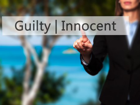 fair trial: Guilty Innocent - Businesswoman hand pressing button on touch screen interface. Business, technology, internet concept. Stock Photo Stock Photo