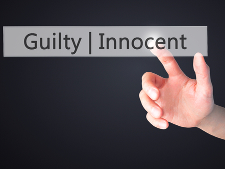 presumption: Guilty Innocent - Hand pressing a button on blurred background concept . Business, technology, internet concept. Stock Photo