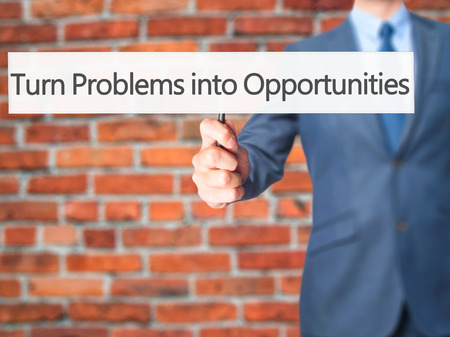 feasible: Turn Problems into Opportunities - Businessman hand holding sign. Business, technology, internet concept. Stock Photo