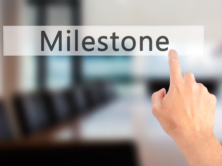solutions freeway: Milestone - Hand pressing a button on blurred background concept . Business, technology, internet concept. Stock Photo