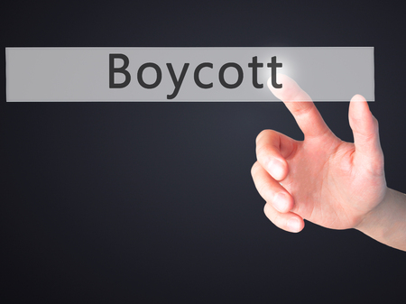 denying: Boycott - Hand pressing a button on blurred background concept . Business, technology, internet concept. Stock Photo Stock Photo
