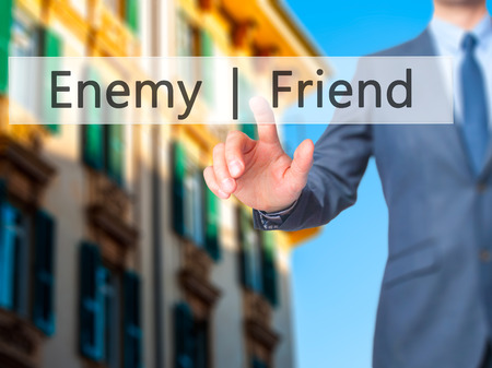 Enemy  Friend - Businessman hand pressing button on touch screen interface. Business, technology, internet concept. Stock Photo Stock Photo