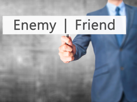 Enemy  Friend - Businessman hand holding sign. Business, technology, internet concept. Stock Photo