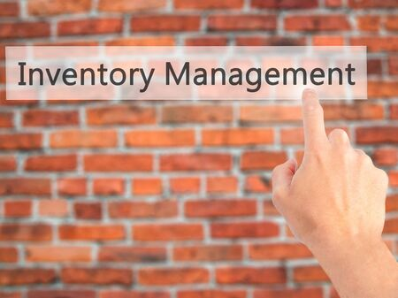 stockroom: Inventory Management - Hand pressing a button on blurred background concept . Business, technology, internet concept. Stock Photo