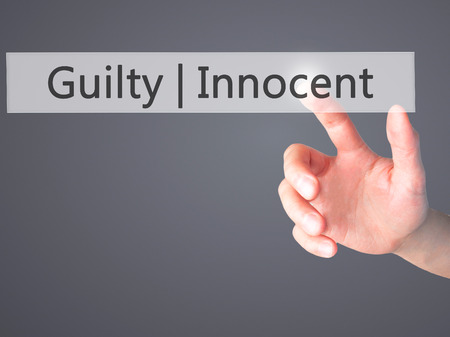 proven: Guilty Innocent - Hand pressing a button on blurred background concept . Business, technology, internet concept. Stock Photo