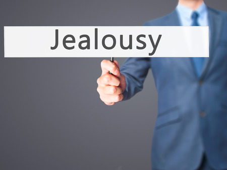 envious: Jealousy - Businessman hand holding sign. Business, technology, internet concept. Stock Photo